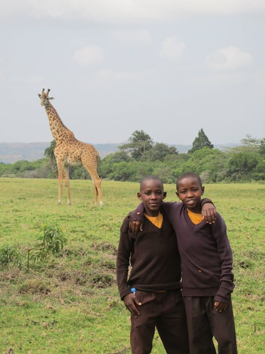 two boys with giraffe